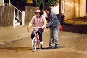 Donny Berger (Adam Sandler) teaching Todd Peterson (Andy Samberg) to ride a bike in Columbia Pictures' comedy THAT'S MY BOY.